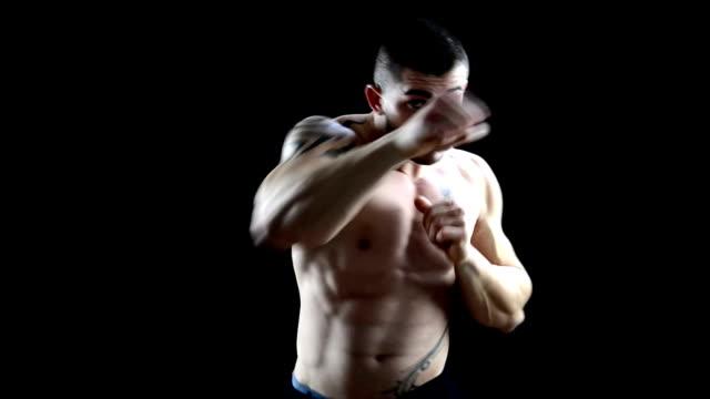 強力な上半身裸、パンチのあるハンサムな男性のボクサーに黒色の背景 ビデオ