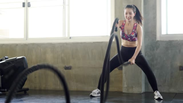 Powerful sporty doing exercise battle rope indoor at fitness gym. woman taking weight loss with machine aerobic for slim and firm health. Healthy sport cardio strong.