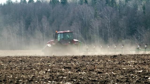 leistungsstarker traktor mit pflug fährt bei heißem wetter durch staubiges und trockenes ackerland. bodenerosion - erodiert stock-videos und b-roll-filmmaterial