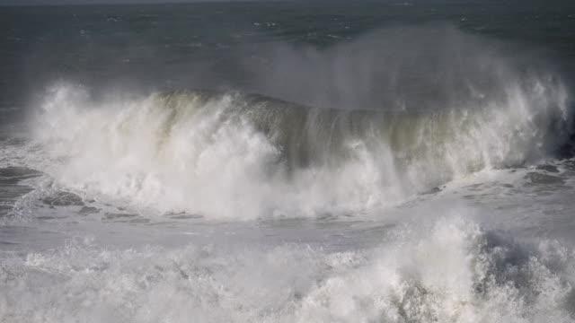 荒れ狂う海の強力な波がゆっくりと転がり、海岸を打ち、白い泡の多くの飛沫を引き起こします。スローモーションショット - 大西洋点の映像素材/bロール