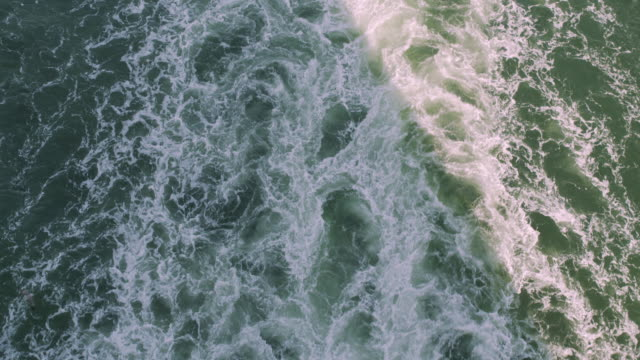 Powerful waves pulled out from fast moving boat, a huge stream of deep blue water with white foam rising up
