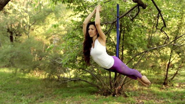 practice of anti gravity fly yoga with hammock - trykot filmów i materiałów b-roll