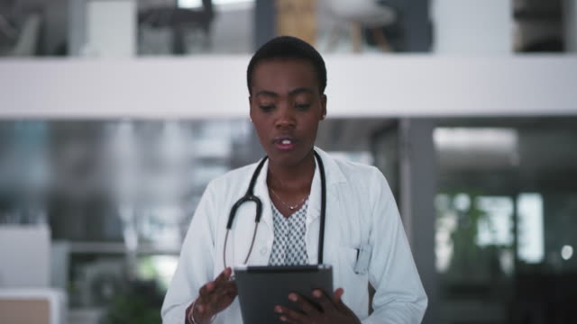 Practicing medicine the smart way 4k video footage of an attractive young female doctor using a digital tablet while walking through a hospital female doctor stock videos & royalty-free footage