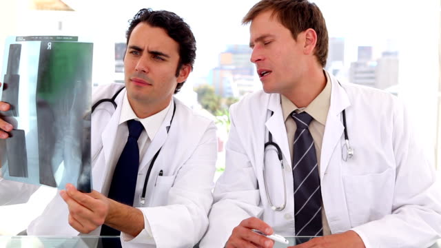 Practitioners seriously looking at an x-ray video