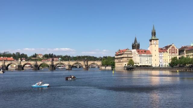 vidéos et rushes de rivière de prague vltava avec pont charles et bateaux de plaisance - prague