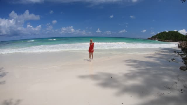 Praslin Seychelles model walking Elegant lifestyle woman in red at Anse Kerlan, Seychelles walking on the shore. Kerlan Beach in Praslin is famous for spectacular sunsets on Cousine and Cousin islands. Luxury holidays cousin stock videos & royalty-free footage