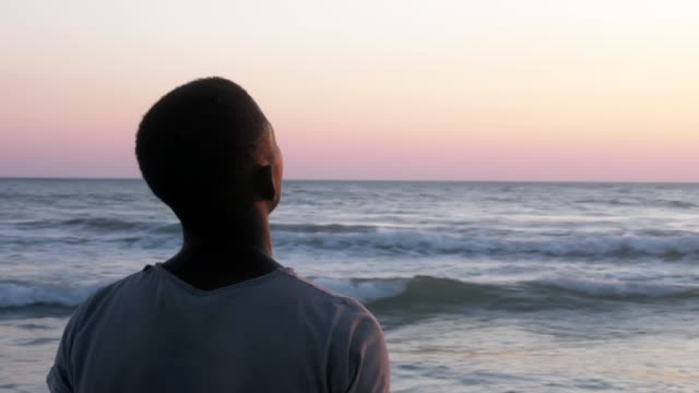 prayer, faith, god. young african man on the beach praying looking at the sky - бог стоковые видео и кадры b-roll