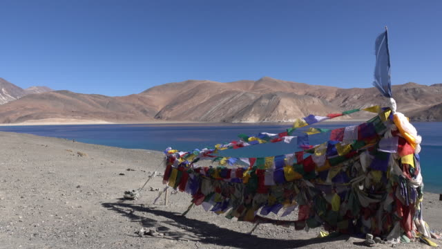 Prayer flags at Pangong Lake with mountain and blue sky, Ladakh, North India video