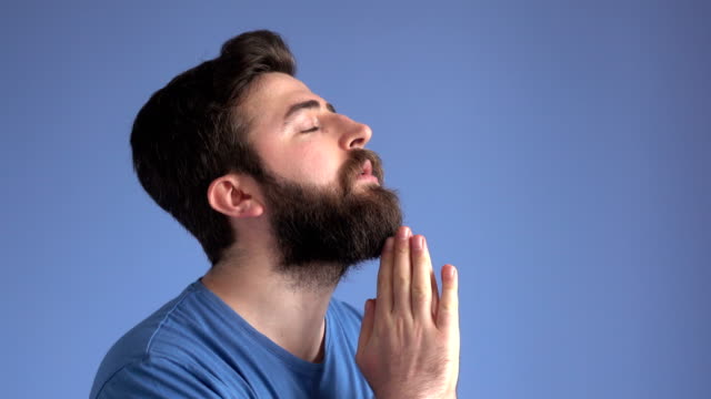 Praying And Contemplating Adult Man On Blue Background video