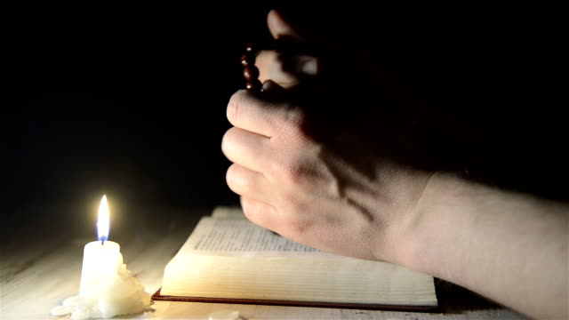 praying hands over a holy book