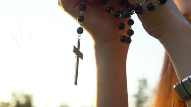 beten mit dem rosenkranz kreuz - religiöses symbol stock-videos und b-roll-filmmaterial