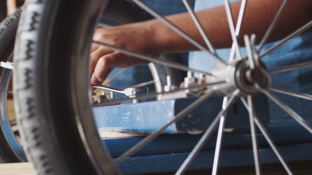 Pre teen boy using a spanner to tighten a nut on a bolt, to attach a wheel to his racing kart, close up, mid section detail, seen through spokes of a wheel Pre teen boy using a spanner to tighten a nut on a bolt, to attach a wheel to his racing kart, close up, mid section detail, seen through spokes of a wheel go cart stock videos & royalty-free footage