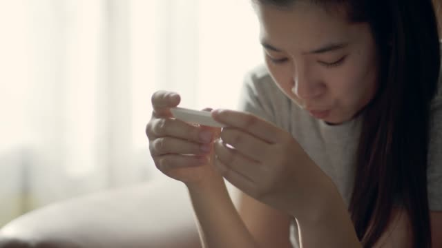 pregnancy concept , young asian woman with a pregnancy test positive result at sofa in home - family planning stock videos and b-roll footage
