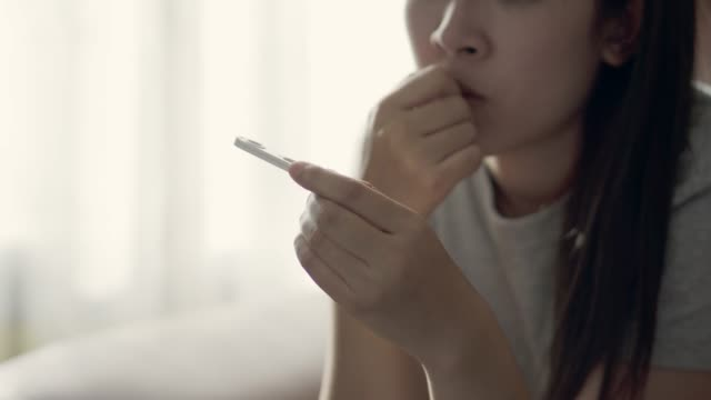 vídeos y material grabado en eventos de stock de concepto de embarazo, joven mujer asiática con una prueba de embarazo resultado positivo en el sofá en casa - planificación familiar