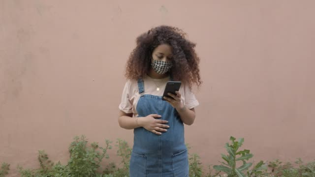 Pregnant afro hair woman in the city wearing a cloth protective mask