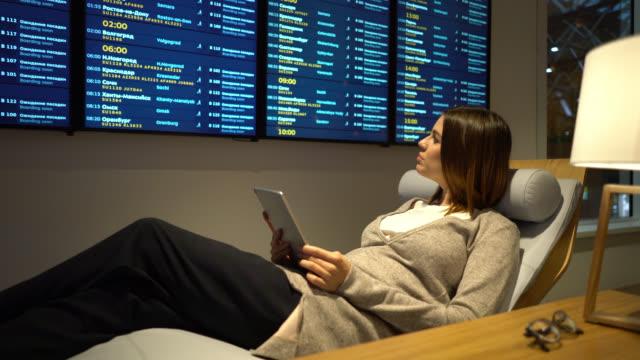 stockvideo's en b-roll-footage met zwangere zakenvrouw ontspannen in de vip-lounge van de luchthaven met behulp van tablet en kijken naar het vluchtschema - vliegveld vertrekhal
