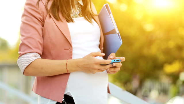 Pregnant business woman using smartphone video