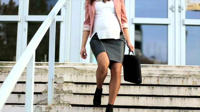 Pregnant business woman walking down stairs video