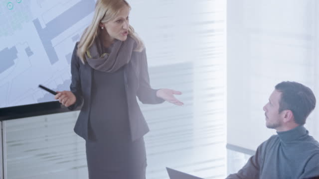 pregnant caucasian architect explaining details of the plans shown on the large screen to her colleagues in conference room - leanincollection stock videos & royalty-free footage