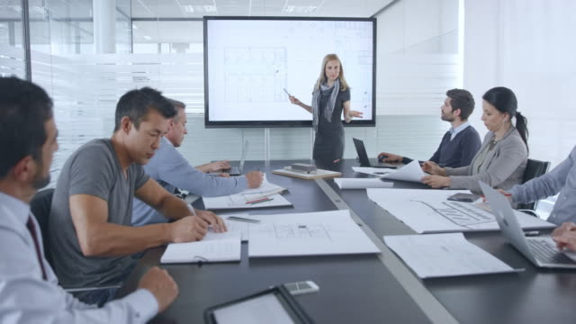 pregnant caucasian architect giving a presentation of her plans to her colleagues in the meeting room - leanincollection stock videos & royalty-free footage