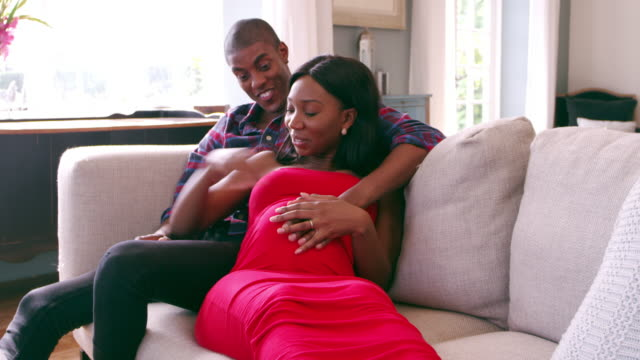 Pregnant Couple At Home Relaxing On Sofa Shot On R3D video
