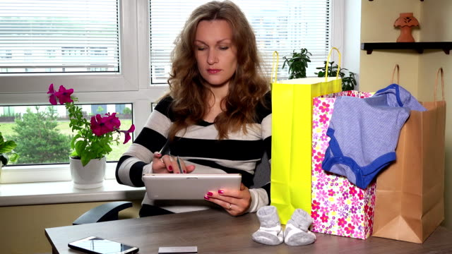 pregnant female shopping online website on wooden table and many shopping bag video