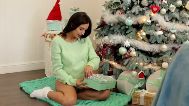 Pregnant girl near the Christmas tree with a gift. video