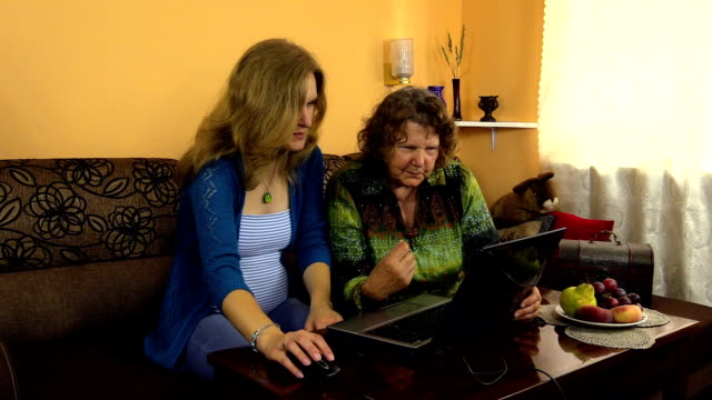 Mujer embarazada granddaughter abuela con ayuda de ordenador - vídeo