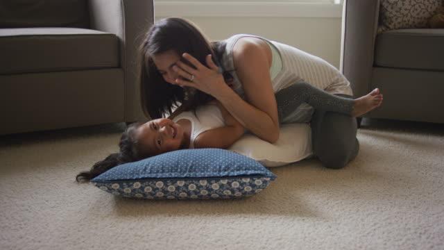 pregnant hispanic mother giving her daughter kisses - fare il solletico video stock e b–roll