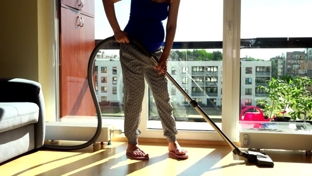 Pregnant house wife with big tummy hoover vacuum clean room in flat house video