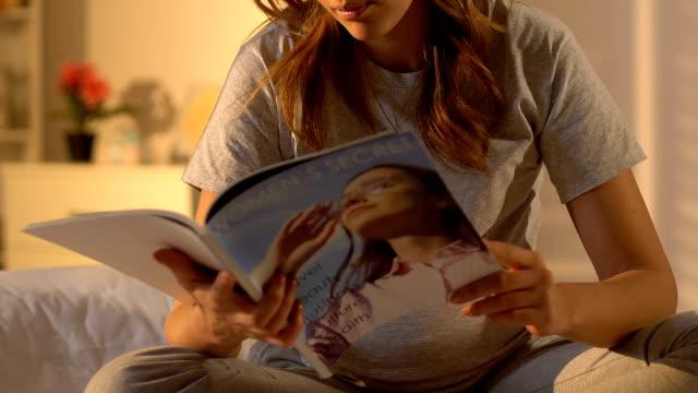 stockvideo's en b-roll-footage met zwangere lady reading magazine, tips voor vrouwen gezondheid tijdens trimester, pasgeboren - woman home magazine