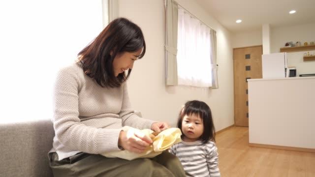 妊娠中の母親と彼女の娘は、彼女の期待の赤ちゃんのための贈り物を開きます - プレゼント点の映像素材/bロール