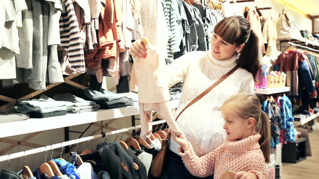 pregnant mother and small daughter choosing clothes video
