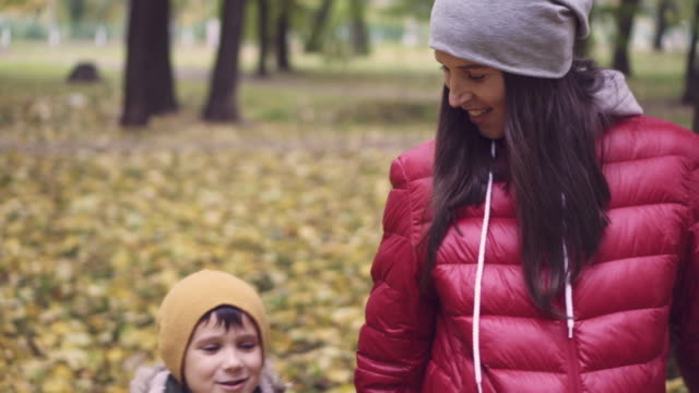 Pregnant mother and son walking in park video