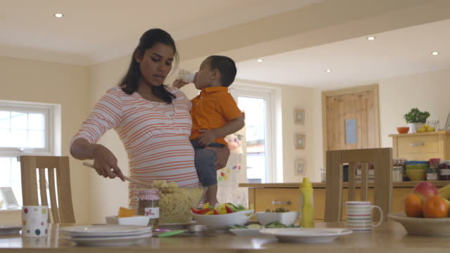 Pregnant Mother Carrying Son Whilst Making Salad In Kitchen video