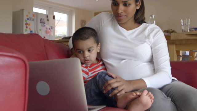 Pregnant Mother Looks At Laptop On Sofa With Son video