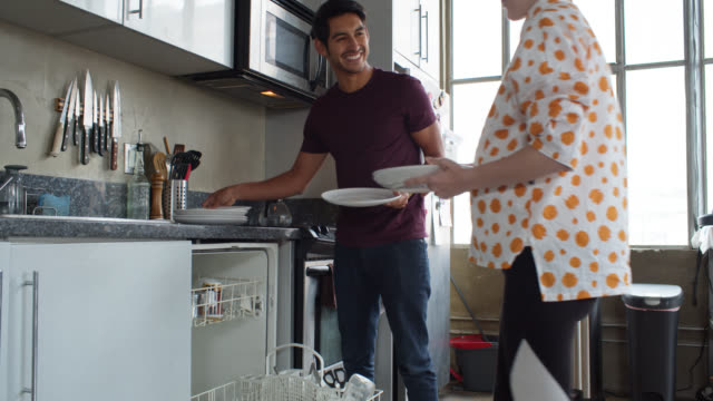 Pregnant Woman and Boyfriend Loading Dishwasher in Loft Apartment A young heterosexual couple at home together in their urban loft apartment, loading the dishwasher and cleaning up after a meal. The woman is pregnant. dishwasher stock videos & royalty-free footage