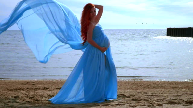 Pregnant woman beach. Pregnancy concept. Pregnant lady in blue dress