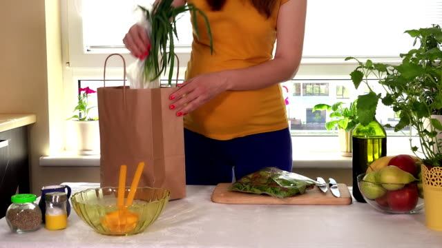pregnant woman carry bags with organic vegetables and unload on kitchen table video