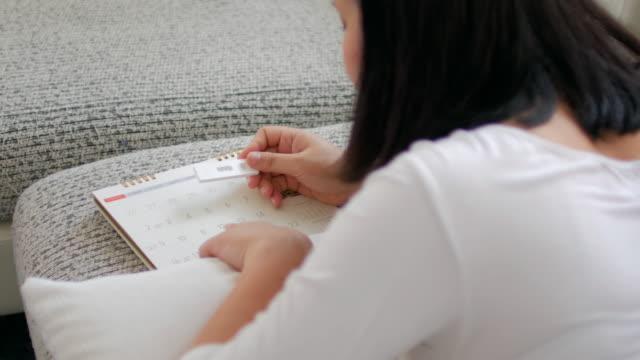 schwangere frau überprüfen kalender mit schwangerschaftstest - familienplanung stock-videos und b-roll-filmmaterial