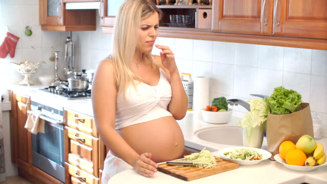 pregnant woman cuts cabbage on wooden board and cut her finger - gusto aspro video stock e b–roll