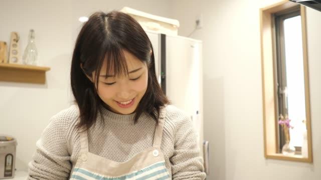 vidéos et rushes de tomate de coupe de femme enceinte dans la cuisine - cuisine non professionnelle
