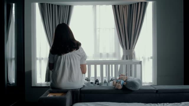 vídeos de stock, filmes e b-roll de mulher grávida decoração berço com celular no quarto de cama. - mobile