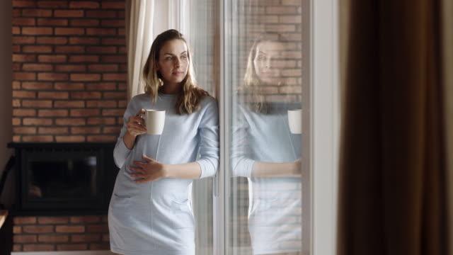 schwangere frau trinkwasser durch fenster zu hause - schwanger stock-videos und b-roll-filmmaterial