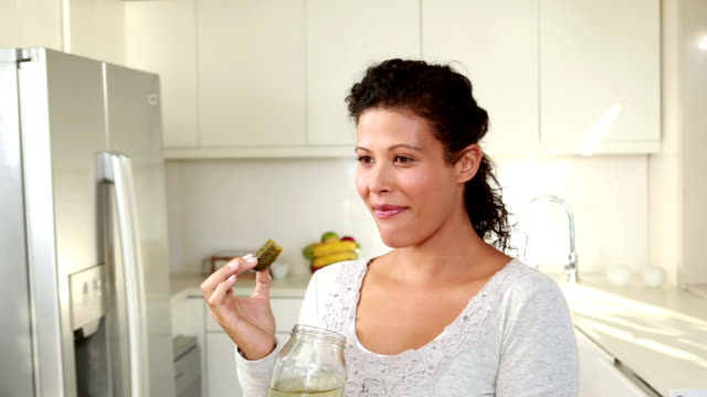 Pregnant woman eating pickles in kitchen Pregnant woman eating pickles in kitchen in high quality 4k format pickle stock videos & royalty-free footage