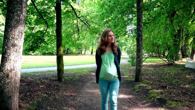 妊娠中の女性妊娠中の母親の公園の木の路地を歩く ビデオ