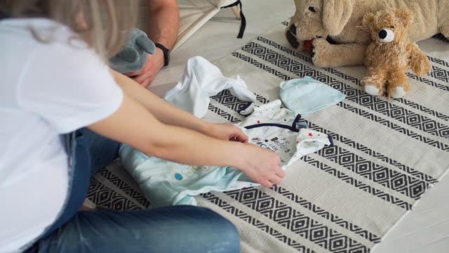 pregnant woman folding baby clothes at home - abbigliamento da neonato video stock e b–roll