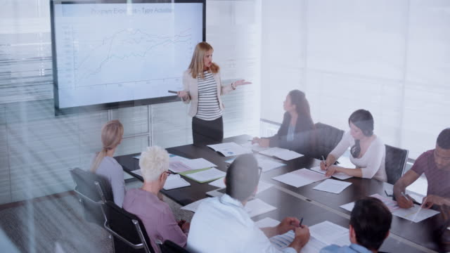 pregnant woman giving a financial presentation to her colleagues in the conference room - leanincollection stock videos & royalty-free footage