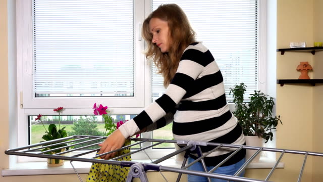 Pregnant woman hang laundry at home Pregnant woman hang laundry at home. Static closeup shot. 4K UHD hanging stock videos & royalty-free footage