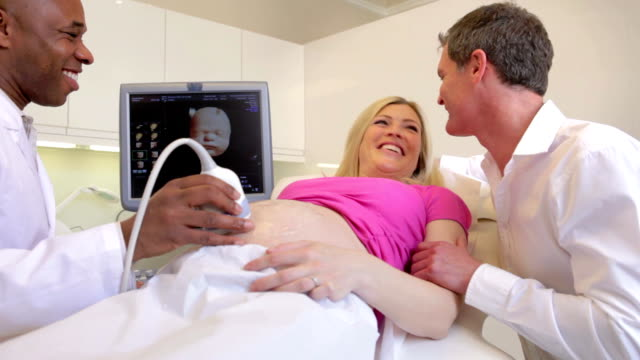 Pregnant Woman Having 4D Ultrasound Scan With Partner video